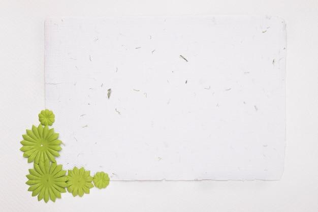Pusty biały papier teksturowany ozdobiony zielonymi kwiatami na tle