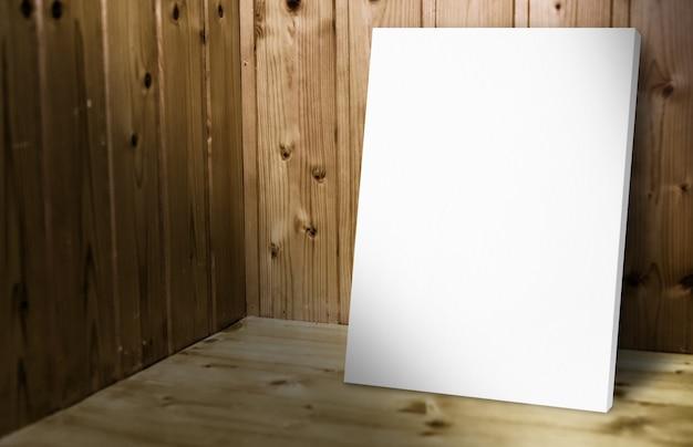 Pusty biały plakat opiera przy drewnianą ścianą w ciemnym deska drewna pokoju