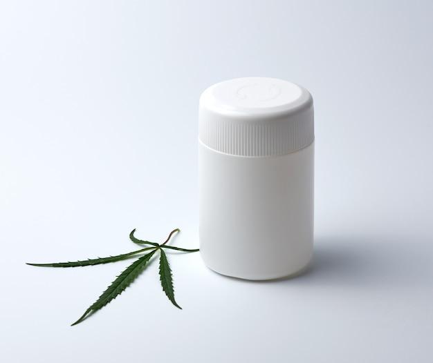 Pusty biały plastikowy słój medyczny na pigułki i zielony liść konopi
