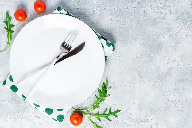 Pusty biały talerz ceramiczny i sztućce na szarym betonowym stole, widok z góry, płaskie ułożenie.