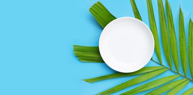 Pusty biały talerz ceramiczny na tropikalnych liściach palmowych na niebieskim tle. widok z góry