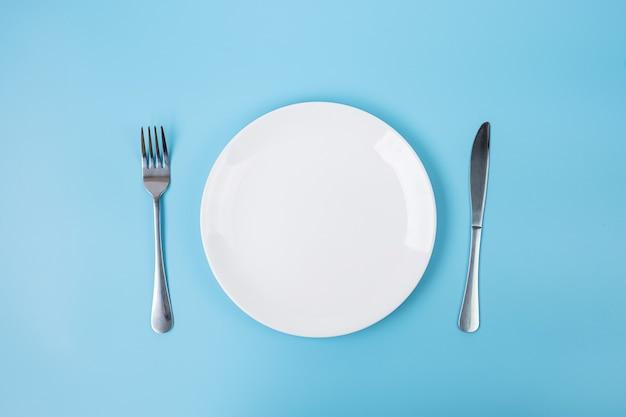 Pusty biały talerz ceramiki z nożem i widelcem na niebieskim tle