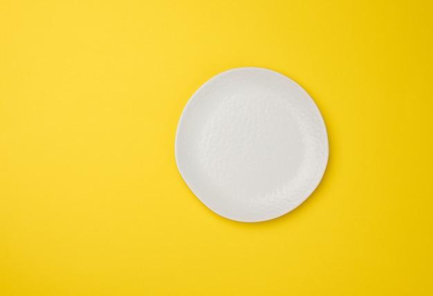 Pusty biały talerz na białym żółtym tle, widok z góry