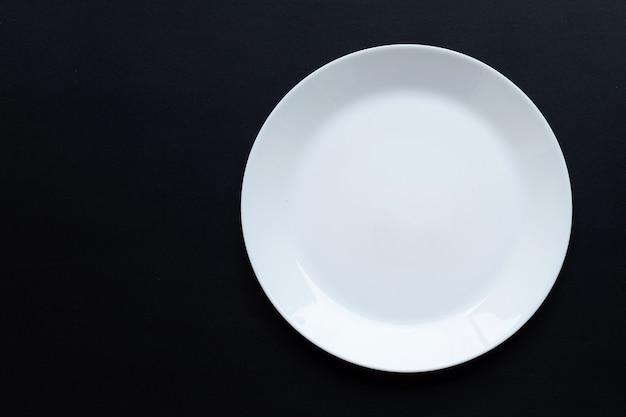 Pusty biały talerz na ciemnej powierzchni. widok z góry
