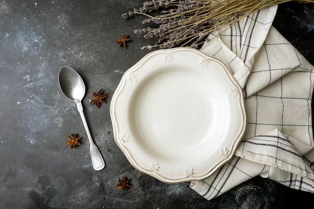 Pusty biały talerz na ciemnym szarym tle z łyżką