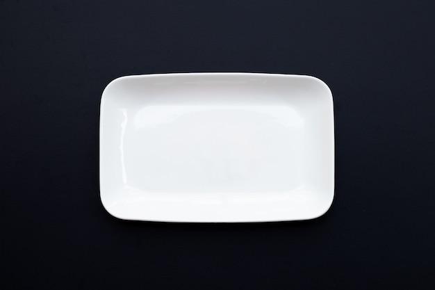 Pusty biały talerz na ciemnym tle drewnianych.