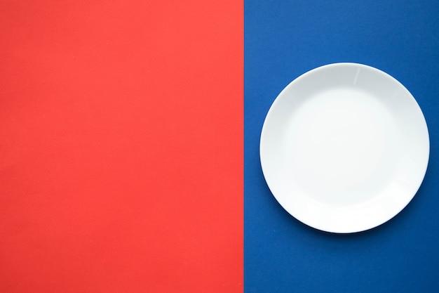Pusty biały talerz na czerwono-niebieskim stole, stół do serwowania dzieł sztuki