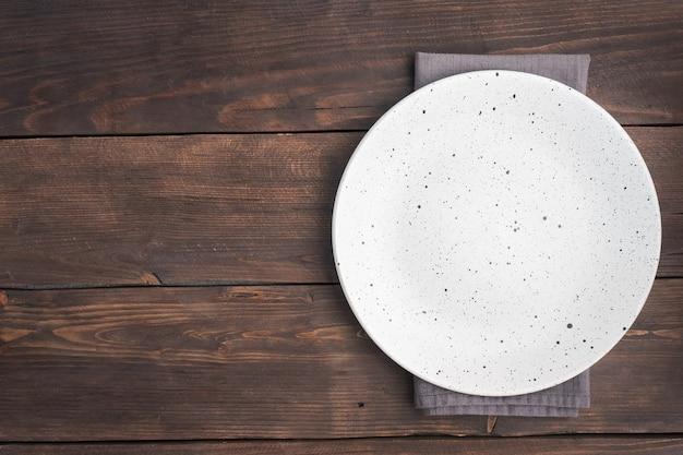Pusty biały talerz na drewnianym tle rustykalnym. widok z góry z miejsca na kopię.
