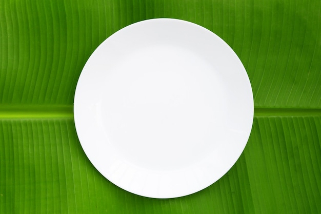 Pusty biały talerz na liściu bananowca