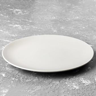 Pusty biały talerz na szorstkiej powierzchni