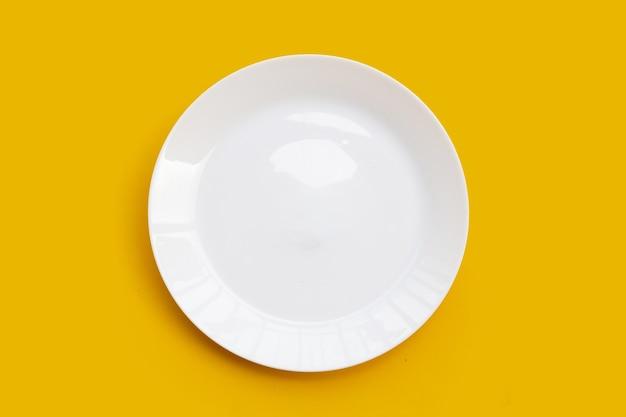 Pusty biały talerz naczynia na żółtej powierzchni.
