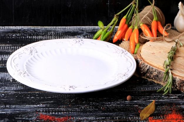 Pusty biały talerz ostra papryka na ciemnym starym drewnianym stołowym pikantność retro roczniku projektuje