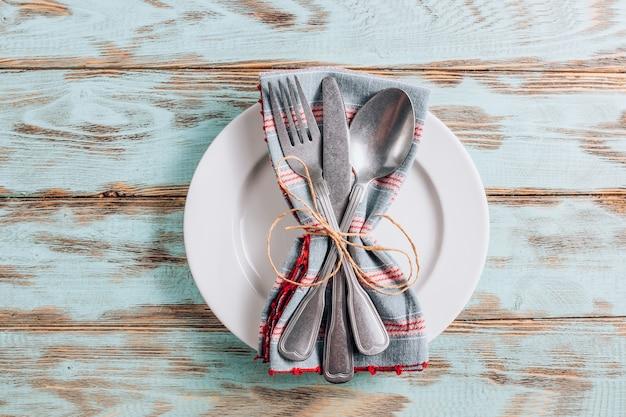 Pusty biały talerz z sztućcami i serwetką na prosty drewniany stół.