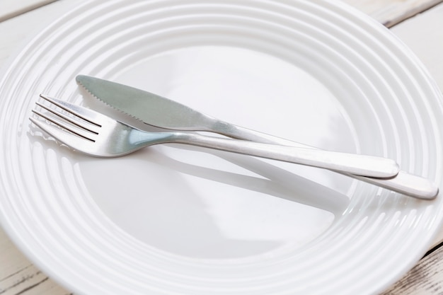 Pusty biały talerz z urządzeniami na odrętwiałym stole. widok z góry.