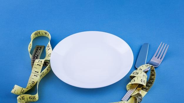 Pusty biały talerz z zawiązaną żółtą taśmą pomiarową. koncepcja utraty wagi. zbliżenie sztućców.