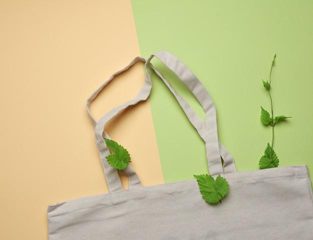 Pusty biały tekstylny bawełniany torba na zakupy wielokrotnego użytku na zielonym tle