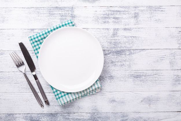 Pusty bielu talerz, cutlery na drewnianym tle i. skopiuj miejsce widok z góry