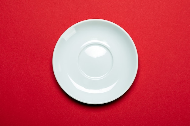 Pusty bielu talerz odizolowywający na czerwieni powierzchni