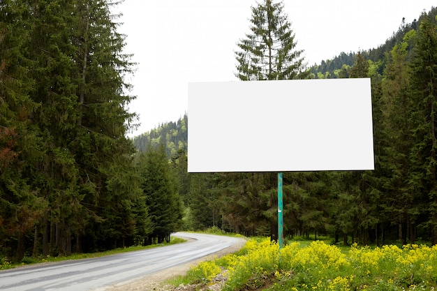 Pusty billboard lub duża deska na poboczu drogi z zielonym lasem i wzgórzami. reklama puste, makieta