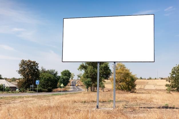 Pusty billboard na plakat reklamowy w pobliżu asfaltowej drogi i wioski. tło błękitnego nieba i pięknej przyrody.