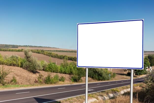 Pusty billboard na plakat reklamowy w pobliżu asfaltowej drogi na błękitnym niebie.