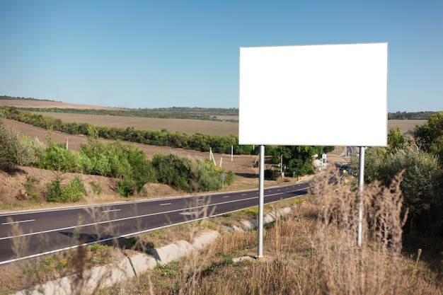 Pusty billboard na plakat reklamowy w pobliżu asfaltowej drogi.