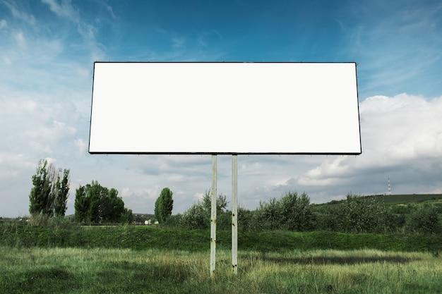 Pusty billboard na plakat reklamowy w zielonym polu omn tle błękitnego nieba.