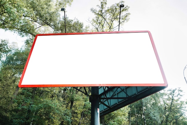 Pusty billboard na tle drzewa