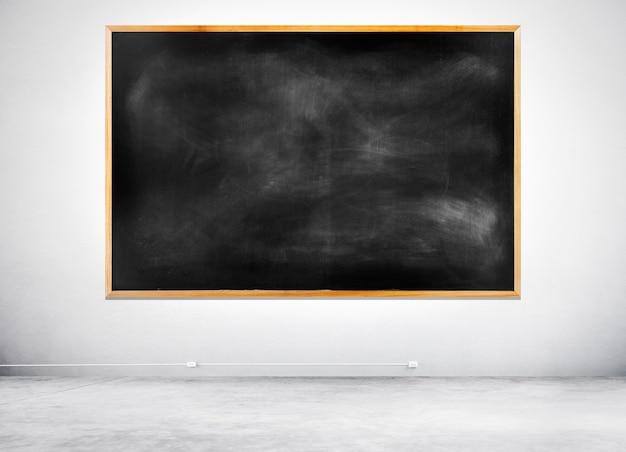 Pusty black chalkboard na białej ścianie