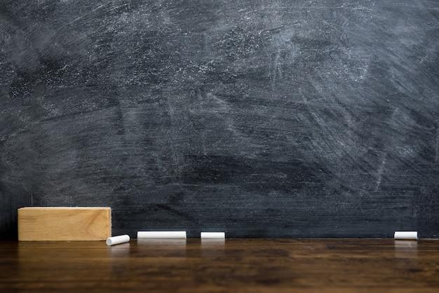 Pusty blackboard lub chalkboard z gumką i kredą na stole