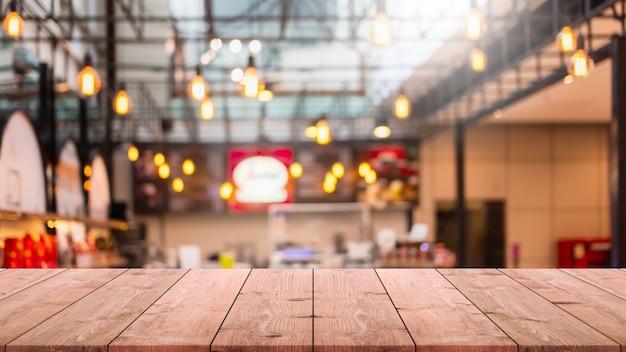 Pusty blat z drewna i niewyraźne wnętrze kawiarni i restauracji