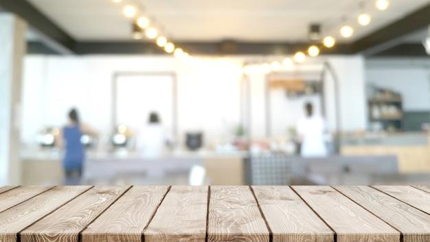 Pusty blat z drewna i niewyraźne wnętrze kawiarni, kawiarni i restauracji