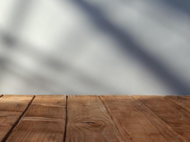 Pusty blat ze ścianą w tle i światłem z okna