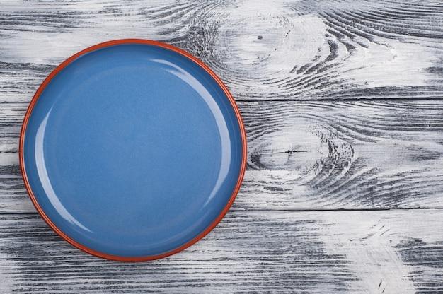Pusty błękita talerz na drewnianym tle