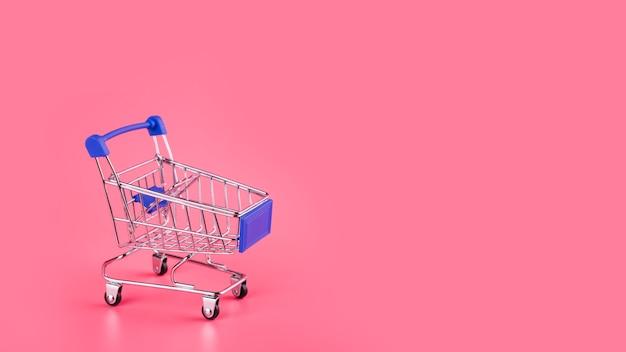 Pusty błękitny wózek na zakupy na różowym tle