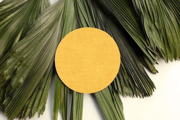 Pusty brązowy okrągły papier na suchych liściach tropikalnych palm