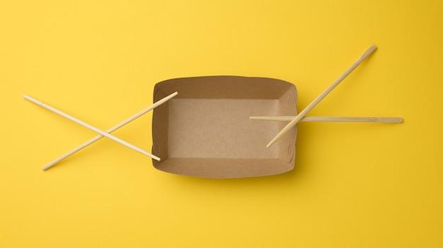 Pusty brązowy papierowy talerz i drewniane pałeczki na żółtym tle, widok z góry. jednorazowa zastawa stołowa, zero waste