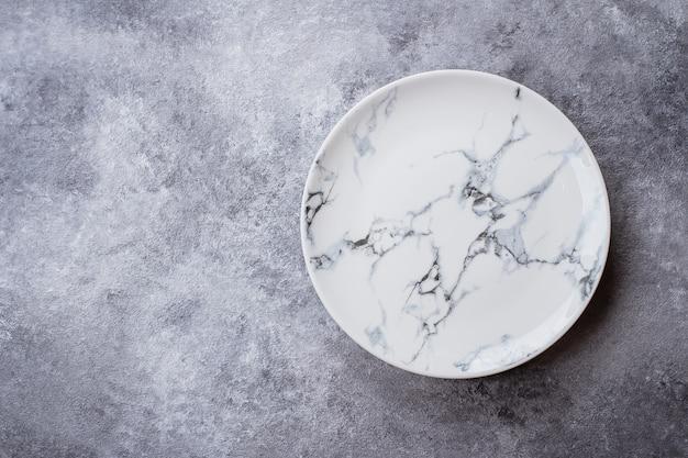 Pusty ceramiczny marmuru talerz na szarość kamienia betonu stołu tle.