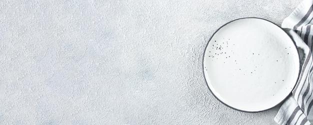 Pusty ceramiczny talerz i kuchenny pasiasty ręcznik na światło kamieniu betonujemy stołowego tło. skopiuj miejsce koncepcja przepisu na menu. widok z góry. leżał płasko. baner do projektu, strona internetowa