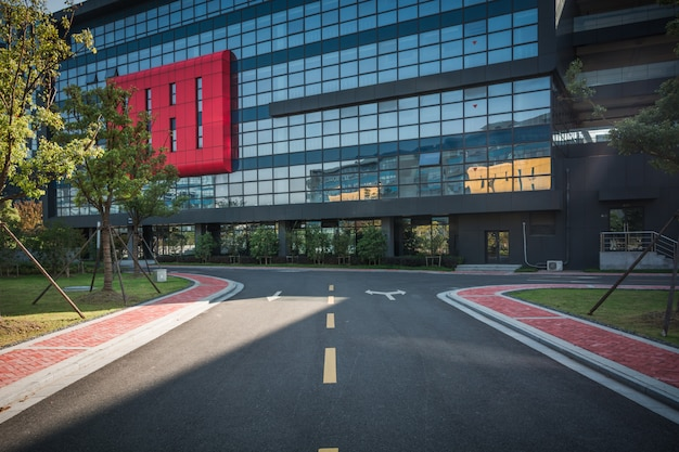 Pusty chodnik z nowoczesną powierzchnią biurowca i błękitne niebo pochmurne podczas wschodu słońca