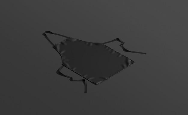 Pusty czarny fartuch z paskiem leżącym na ciemnym tle