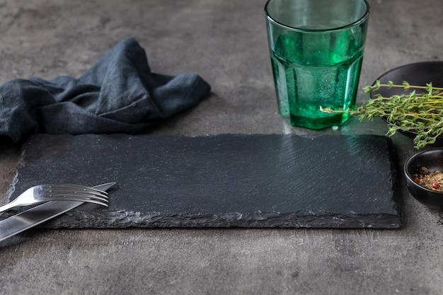 Pusty czarny kamienny talerz na czarnym stole w restauracji