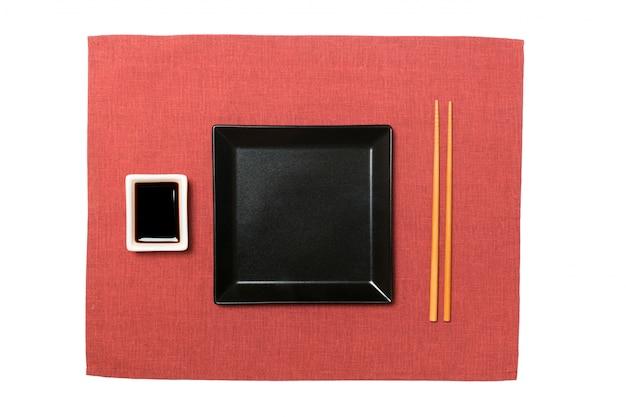 Pusty czarny kwadratowy talerz z pałeczkami do sushi i sosu sojowego na czerwonej serwetce