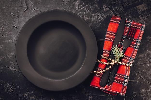 Pusty czarny minimalistyczny talerz i czarne sztućce w świątecznym wystroju