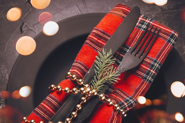 Pusty czarny minimalistyczny talerz i czarne sztućce z świątecznym wystrojem z bliska