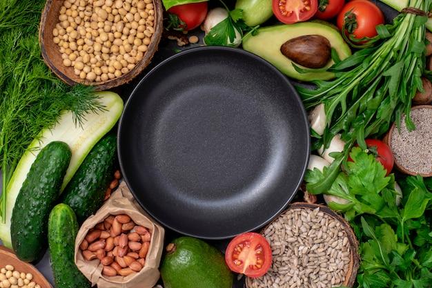 Pusty czarny okrągły talerz z zestawem zdrowej i wegańskiej kaszy, nasion. zdrowe i wegetariańskie menu koncepcji