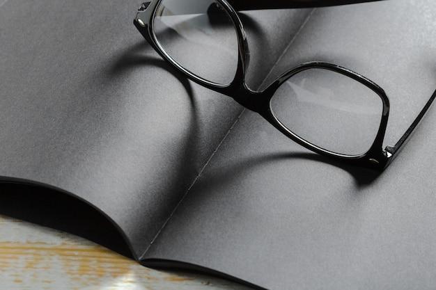 Pusty czarny pamiętnik z okularami