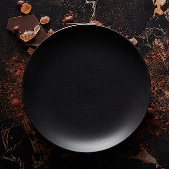 Pusty czarny talerz na ciemnej marmurowej powierzchni. widok z lotu ptaka, z miejsca na kopię.