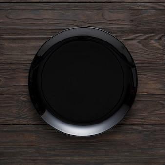 Pusty czarny talerz na drewnianym stole, odgórny widok