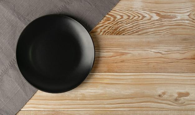 Pusty czarny talerz na drewnianym stole widok z góry z miejsca na kopię